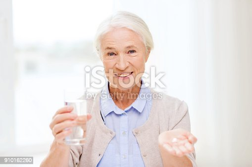 istock happy senior woman with water and medicine at home 910162260