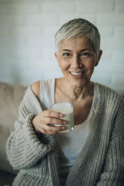feliz mujer senior con bigote de yogurt en casa. - kéfir fotografías e imágenes de stock