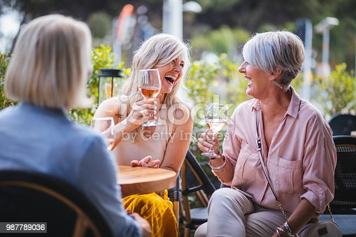 Mature women enjoying a glass of wine, having fun and laughing together at city restaurant