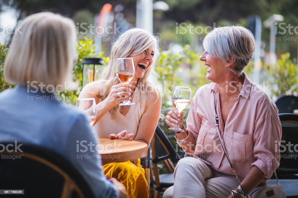 Happy senior women drinking wine and laughing together at restaurant stock photo