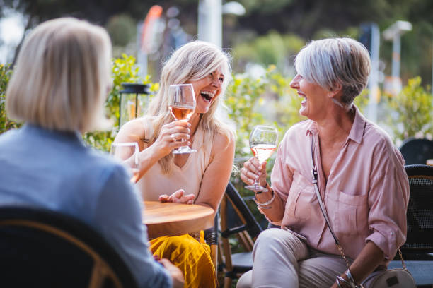 happy senior women drinking wine and laughing together at restaurant - affluent lifestyle stock pictures, royalty-free photos & images