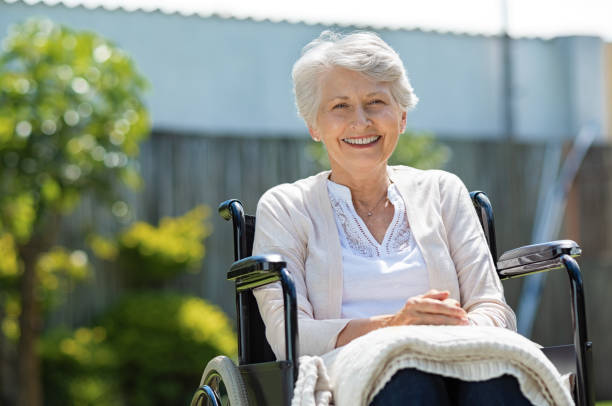 Happy senior women in wheelchair Happy senior woman sitting on wheelchair and recovering from illness. Handicapped mature woman sitting in wheelchair smiling and looking at camera. Portrait of a disabled elderly woman outdoor in a nursing home. retirement community stock pictures, royalty-free photos & images