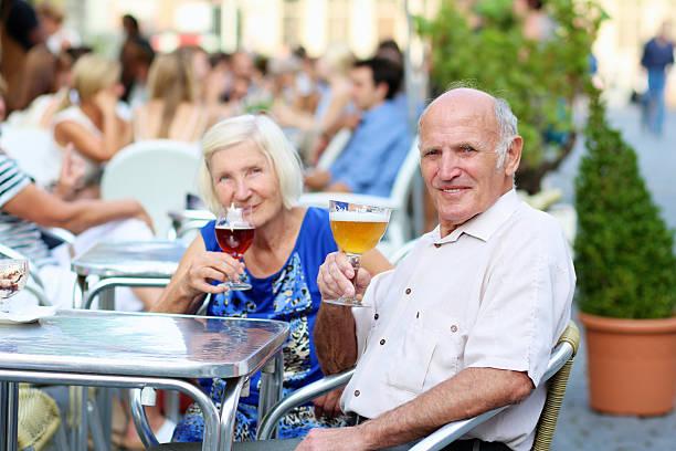 glückliches senior paar trinken im freien street café - bier gesund stock-fotos und bilder