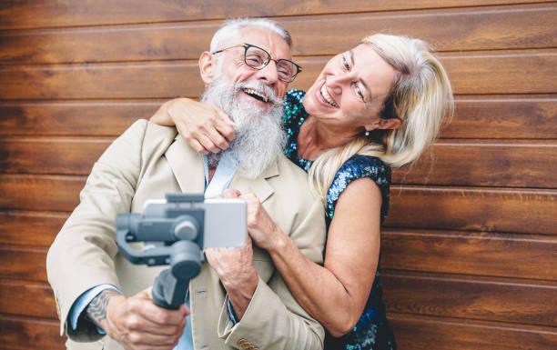 happy senioren paar aufnahme video mit gimbal handy im freien-mature fashion menschen, die spaß mit neuen trends smartphone-apps-holzhintergrund-elderly lifestyle und technologie-konzept - alte tattoos stock-fotos und bilder