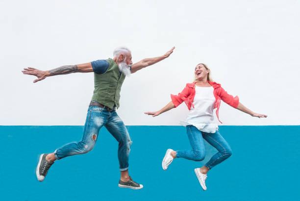 verrücktes paar glücklich senioren springen zusammen im freien - reife trendige leute spaß haben, feiern und tanzen außerhalb - konzept von glück, freiheit, sorglos, liebe und beziehung - ehepaar tattoos stock-fotos und bilder