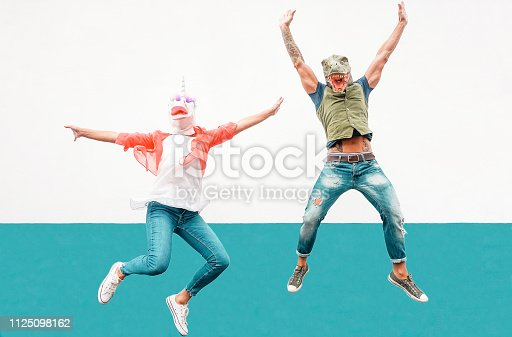 istock Happy seniors crazy couple wearing unicorn and t-rex mask while jumping outdoor - Mature trendy people having fun celebrating outside - Absurd concept of masquerade funny holidays 1125098162
