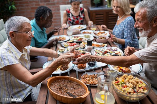 Group of senior friends enjoying in vegan meal in backyard. Sitting by the table and talking.