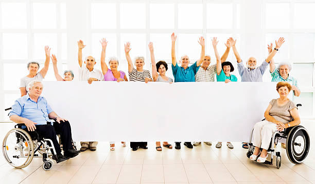 Happy Seniors Holding A Banner Stock Photo Download Image Now Istock