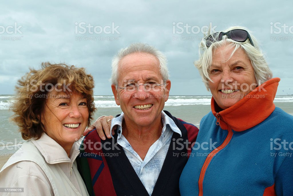Happy seniors on the beach  with waving hair royalty-free stock photo