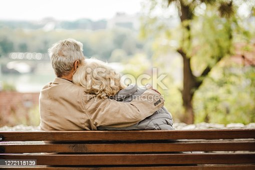 A rearview of a happy senior couple sitting on a bench together in warm clothing