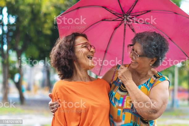 Photo of Happy seniors walking in the rain