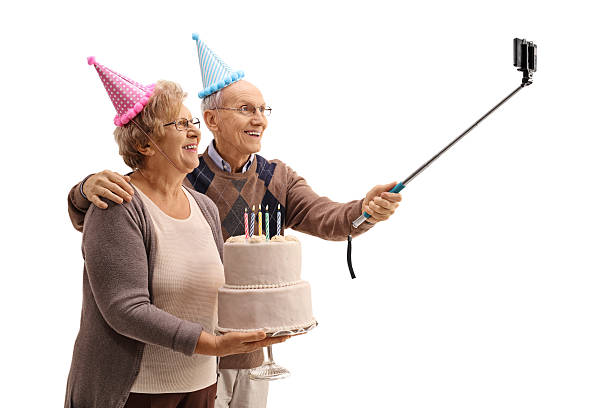 happy seniors with party hats and birthday cake taking selfie - geburtstagstorten bilder stock-fotos und bilder