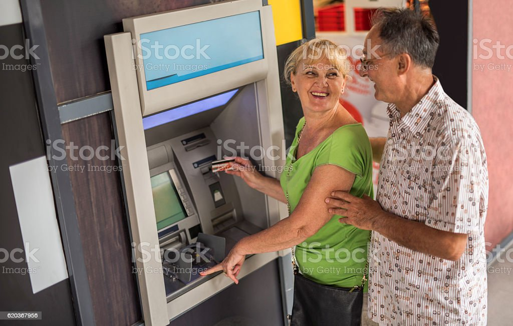 Happy seniors withdrawing money from a cash machine. foto de stock royalty-free