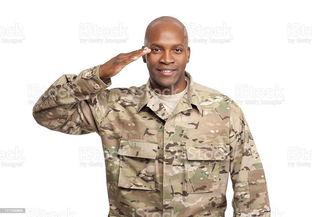 Happy serviceman salutes stock photo