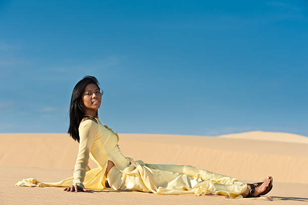 happy sexy lady sitting on sand - ao dai stock photos and pictures