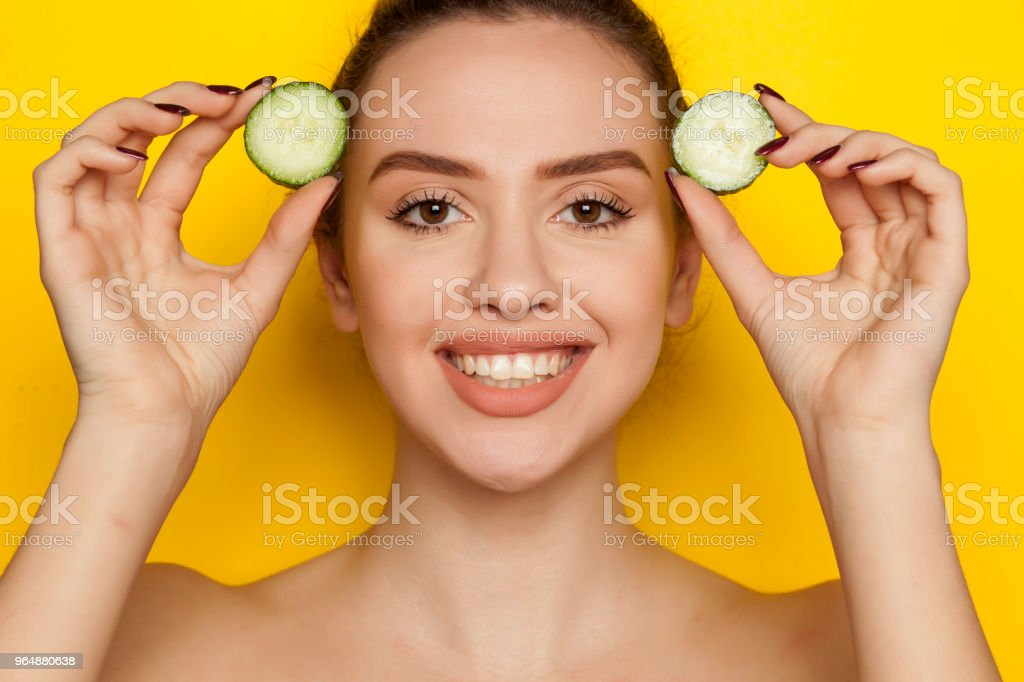 Happy sexy woman posing with slices of cucumber in her hands on yellow background royalty-free stock photo