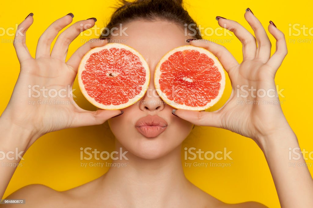 Happy sexy woman posing with slices of red grapefruit on her face on yellow background royalty-free stock photo