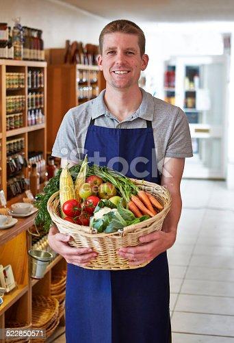 istock Happy shop keeper holding basket of vegetables in delicatessen 522850571