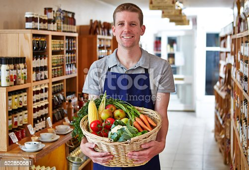 istock Happy shop keeper holding basket of vegetables in delicatessen 522850581