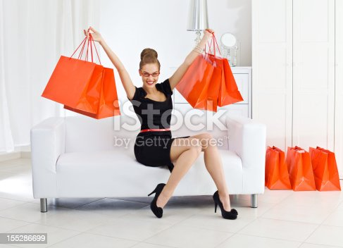 Portrait of an elegant young woman siting on sofa in her room and holding up red shopping bags, smiling at the camera.