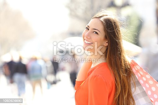 Happy shopper posing holding shopping bags in a street