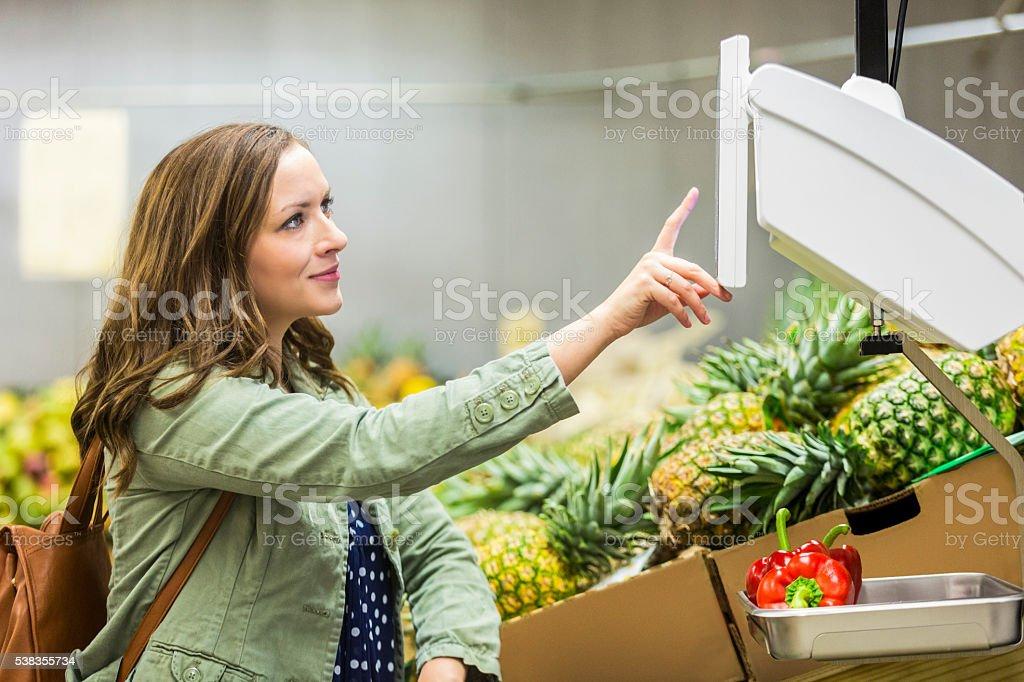 Feliz compras pesaje de la producción - foto de stock
