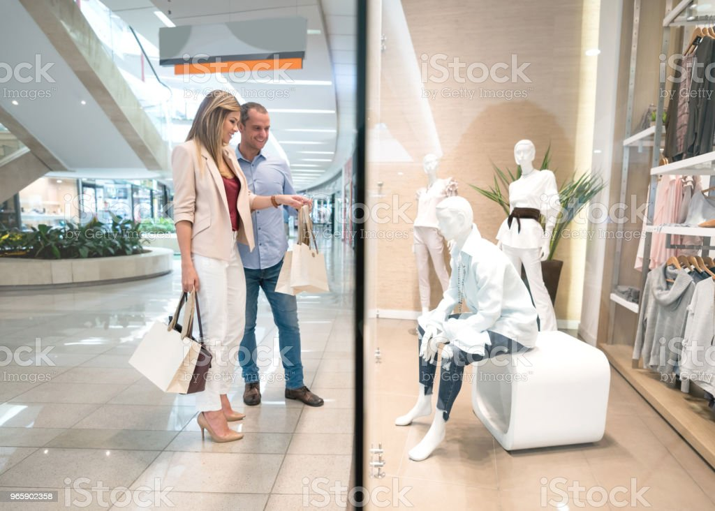 Happy shopping couple pointing at a shop window - Royalty-free 30-39 Years Stock Photo