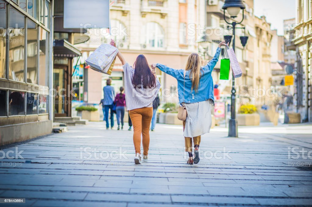 Happy shopping girls, hand in hand, walking city streets with shopping bags royalty-free stock photo