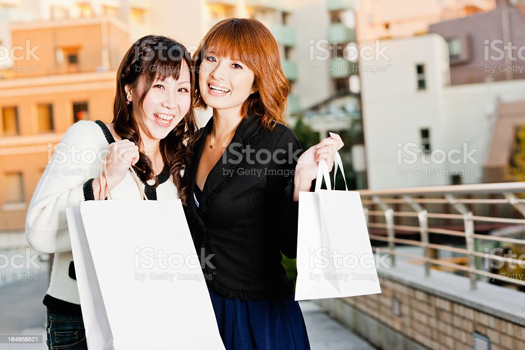 Happy Shopping Japanese Women with Paper Bags in Tokyo royalty-free stock photo