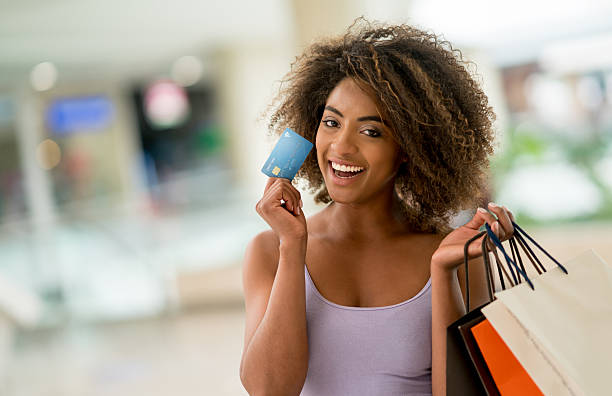 Happy shopping woman holding a credit card stock photo