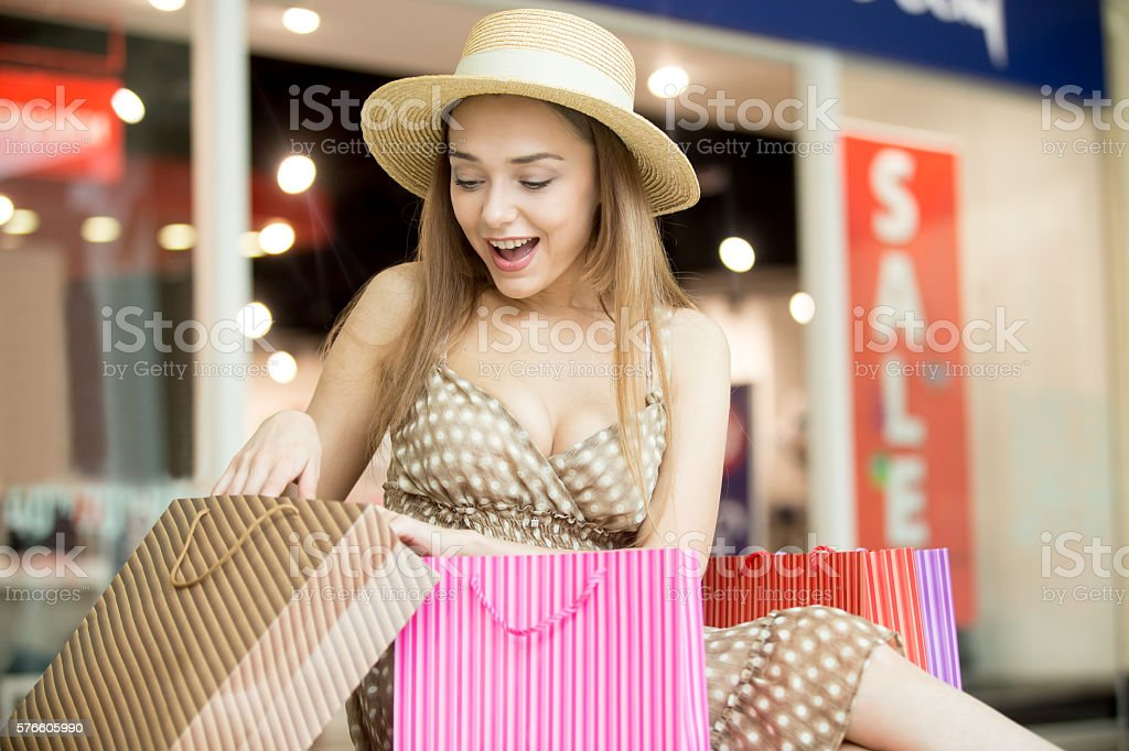 Happy shopping woman looking at her purchase стоковое фото