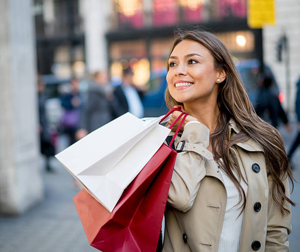 Happy shopping woman Portrait of a happy woman on the street having fun shopping and carrying bags one mid adult woman only stock pictures, royalty-free photos & images