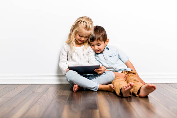 Happy siblings child playing with pc tablet together A Happy siblings child playing with pc tablet together sibling stock pictures, royalty-free photos & images