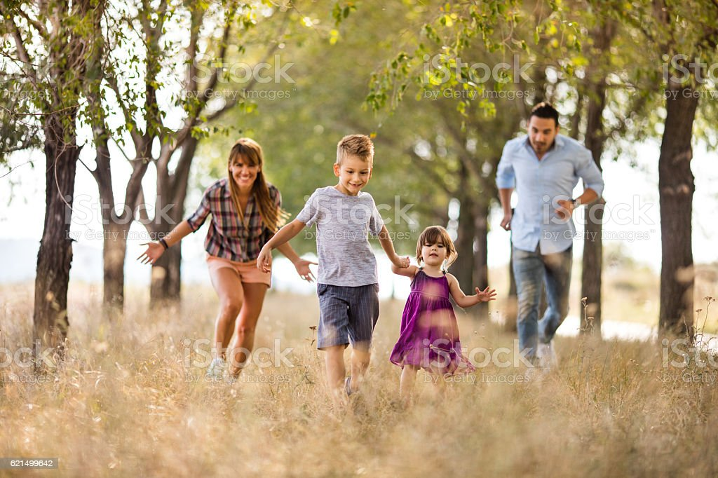 Happy siblings having fun while running with parents in nature. foto stock royalty-free