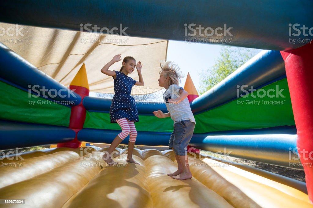 Glücklich Geschwister Springen auf Hüpfburg auf Spielplatz – Foto
