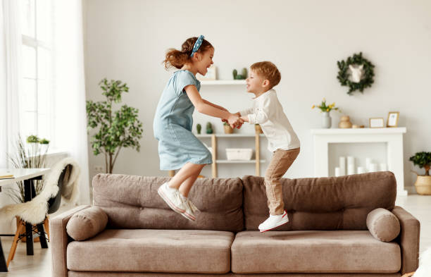 Happy siblings jumping on sofa Side view of cheerful boy and girl holding hands and jumping on couch while having fun at home together brother stock pictures, royalty-free photos & images