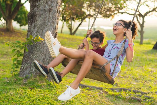 happy siblings playing on the swing - balouço imagens e fotografias de stock