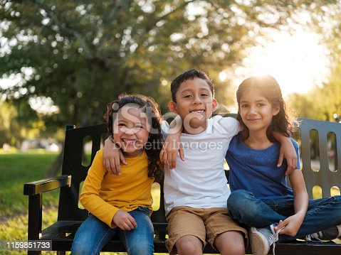 Three happy siblings sitting together outdoors on a park bench while smiling at the camera on a bright and sunny day