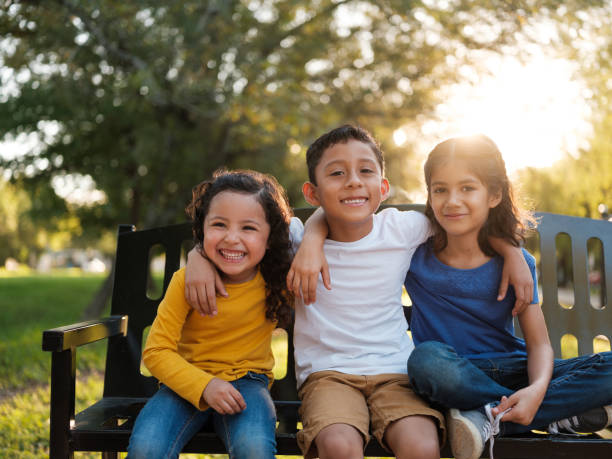 Happy siblings side side by side in the park stock photo