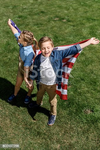istock happy siblings with american flag having fun outdoors, celebrating 4th july - Independence Day 802437256
