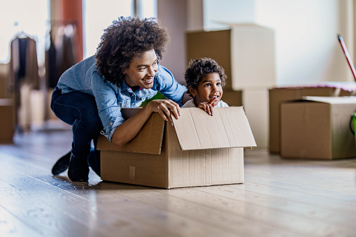 Happy African American mother and her small daughter in cardboard box at their new home.