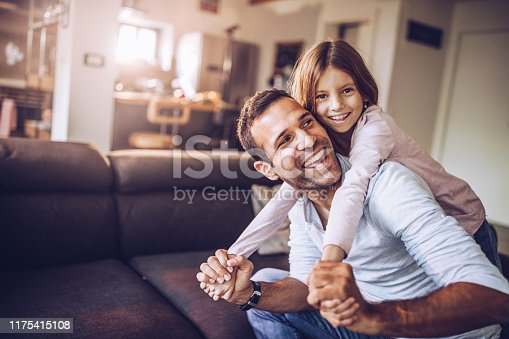 Happy single father and daughter having fun in the living room. Girl is looking at camera.