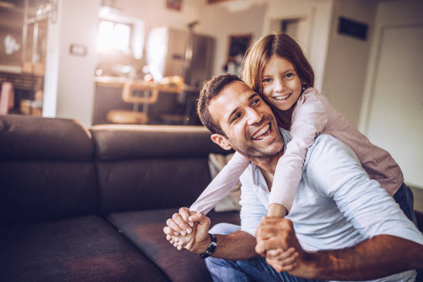 Happy single father having fun with his small daughter at home. stock photo