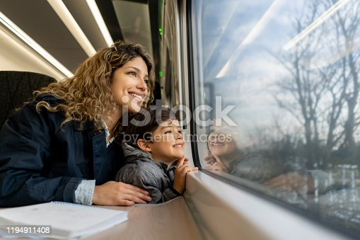 Happy single mother and son looking at the window view both smiling while traveling by train - Lifestyles