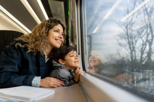Happy single mother and son looking at the window view both smiling while traveling by train Happy single mother and son looking at the window view both smiling while traveling by train - Lifestyles boy looking out window stock pictures, royalty-free photos & images