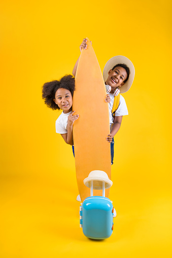 Happy sister and brother standing near surfboard with backpack and suitcase on yellow background
