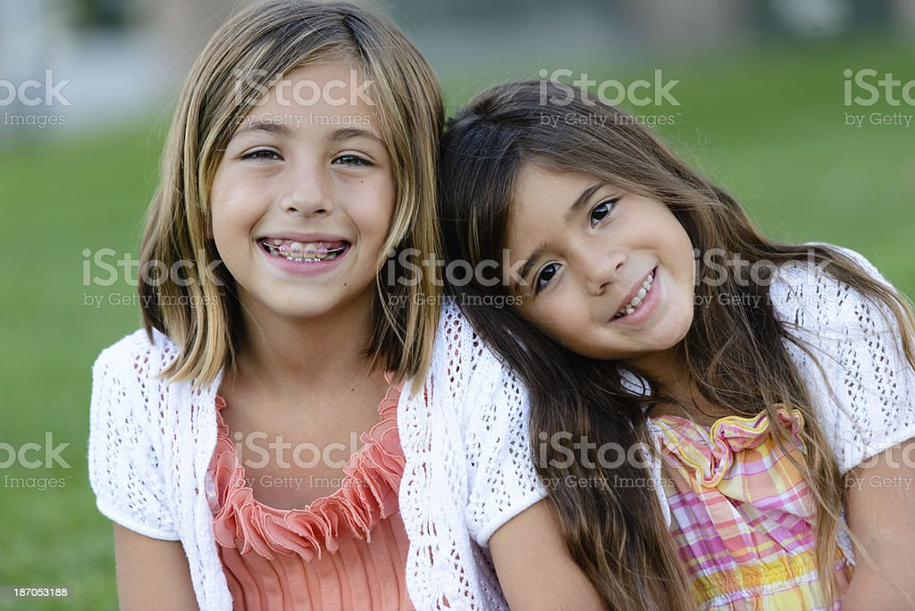 Happy Sisters at the Park Adorable happy girls sitting side by side.  One is resting her head on the other's shoulder.  Could be friends or sisters. 6-7 Years Stock Photo