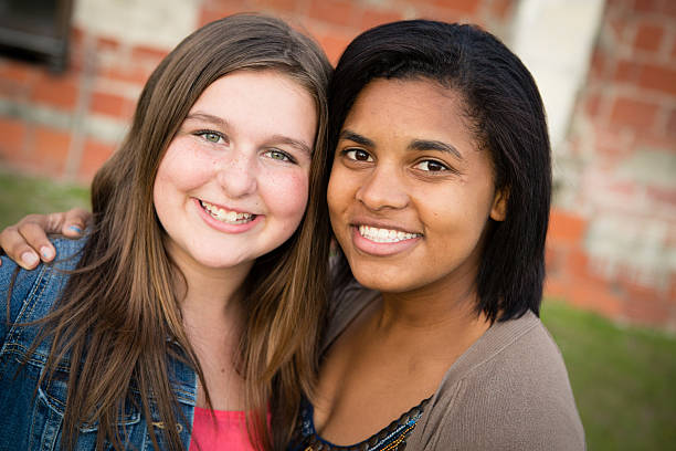 Happy Sisters by Adoption Smiling Together Outside stock photo
