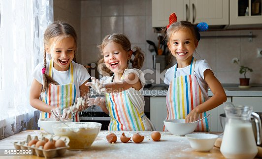 istock happy sisters children girls bake cookies, knead dough, play with flour and laugh 845508996