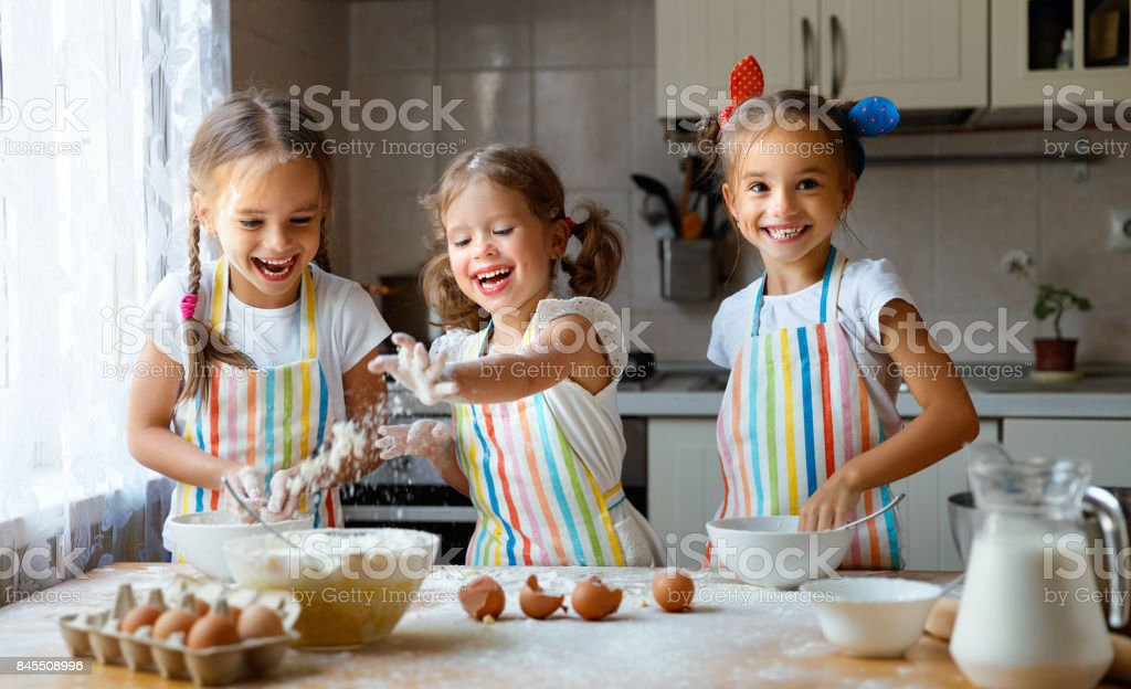 happy sisters children girls bake cookies, knead dough, play with flour and laugh - foto stock